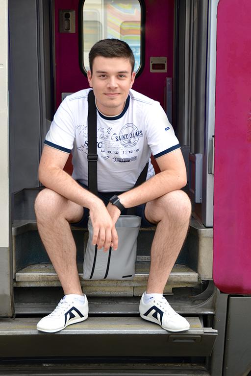 Prise de vue de Théo assis sur les marches d'accès au train OUIGO