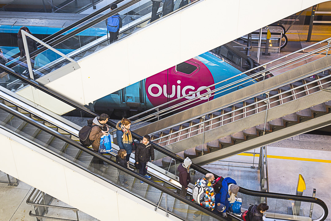 Prise de vue plongeante sur les escalators de la gare de Marne la Vallée avec en fond un train OUIGO